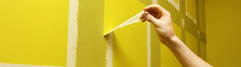 worker man removing masking tape from painting wall; Shutterstock ID 257875010